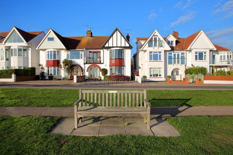 Строка красочных домов, расположенная на морском параде, с деревянной скамьей на переднем плане, Leigh на море стоковое изображение