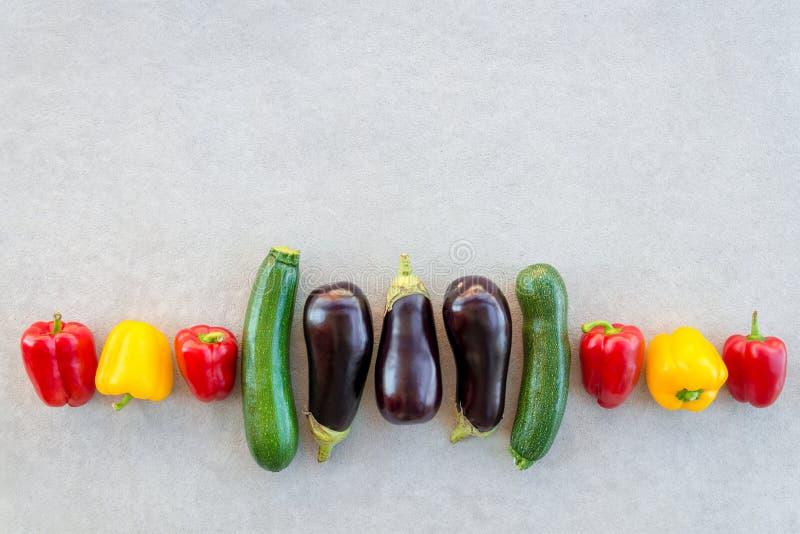Строка красочных овощей лета на конкретной предпосылке стоковые изображения