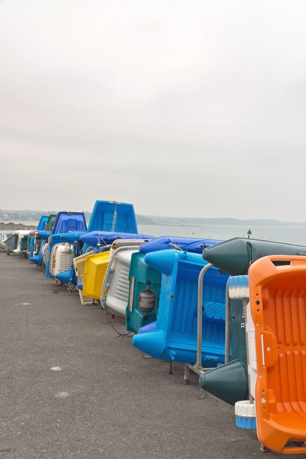 Строка красочных пластичных шлюпок на береге пасмурное небо brittani стоковая фотография rf
