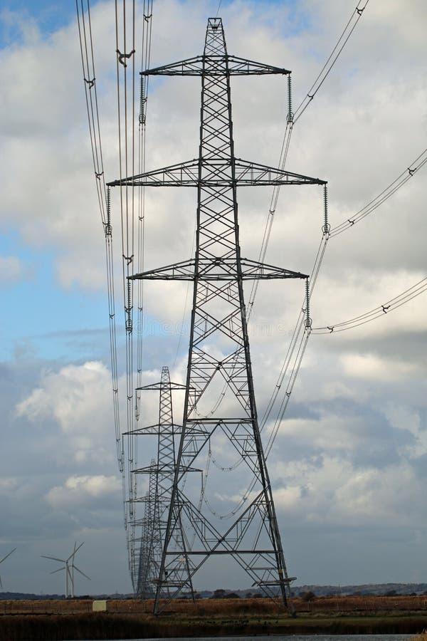Строка национальных опор электричества высокого напряжения решетки стоковые фото