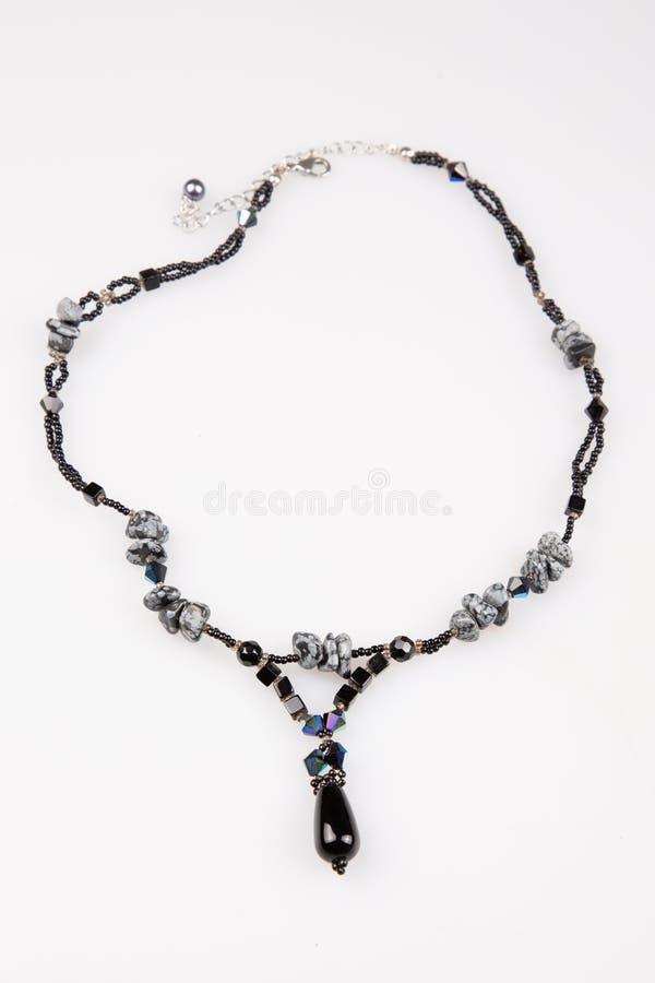 Строка отбортовывает черное ожерелье на белой предпосылке стоковые фото