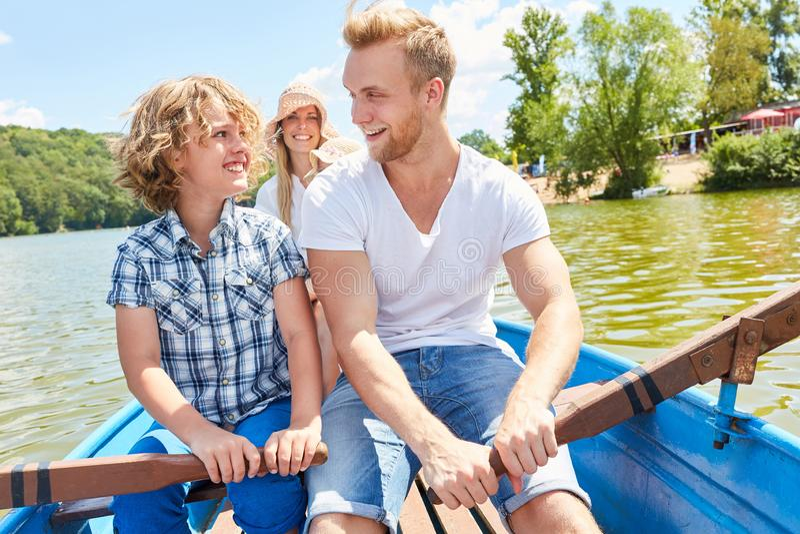 Строка отца и сына совместно в весельной лодке стоковое фото