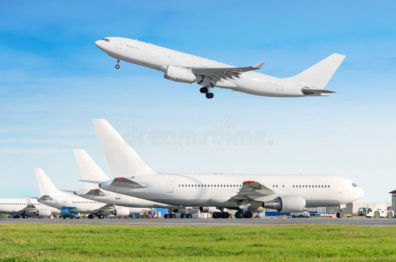Строка пассажирского самолета, самолет припаркованный на обслуживании перед отклонением на авиапорте, другое плоское нажимает наз стоковые фотографии rf