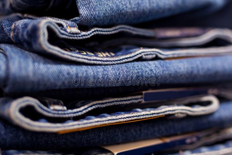 Строка повешенных голубых джинсов в магазине стоковые фотографии rf