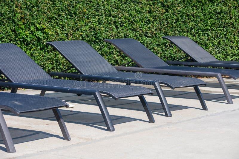 Строка пустых стульев бассейна для лежать вниз с зеленой предпосылкой на солнечный день стоковая фотография rf