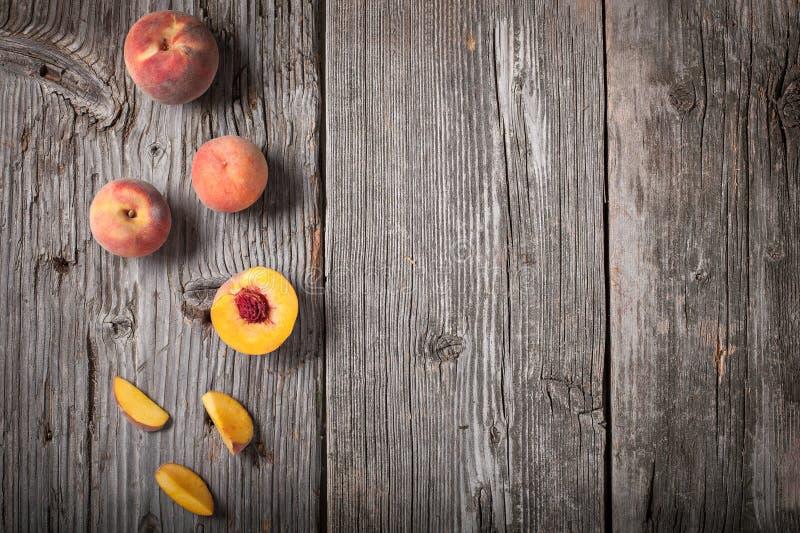 Строка свежо скомплектованных всех и отрезанных персиков на деревянной предпосылке стоковые изображения