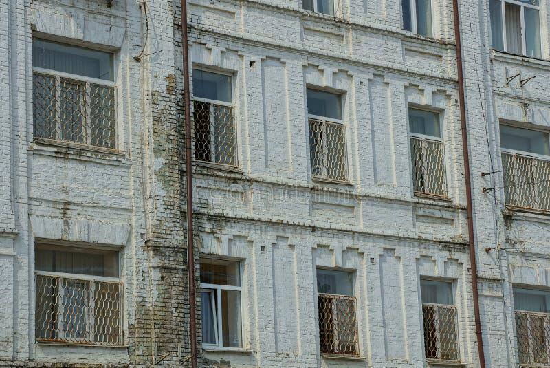 Строка старых окон на серой кирпичной стене дома стоковые фото