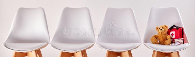 Строка стульев с плюшевым медвежонком и бортовой аптечкой стоковые изображения