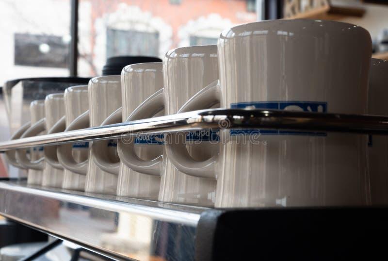 Строка чистых кружек кофе за рельсом Chrome стоковые фотографии rf