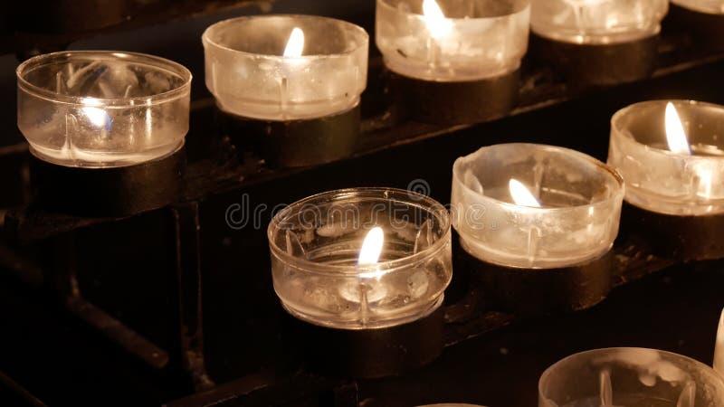 Строки гореть освещенные свечи/tealights в католической христианской церков стоковое фото rf