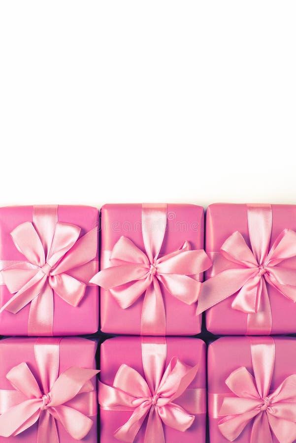 Строки коробок 6 с взгляд сверху пинка a смычка сатинировки орденской ленты подарков положения квартиры стоковые фотографии rf