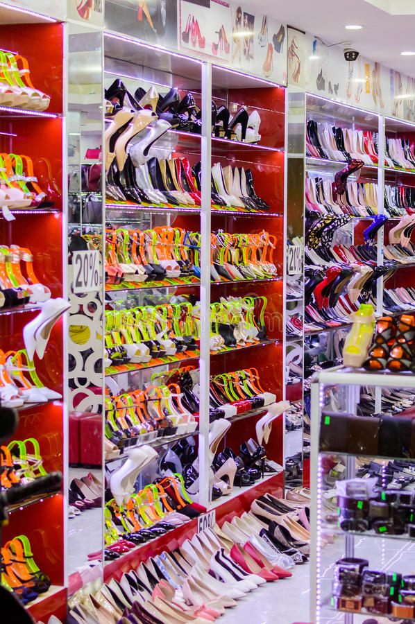 Строки красивых, элегантных, покрашенных ботинок ` s женщин на витринах магазина стоковое изображение rf