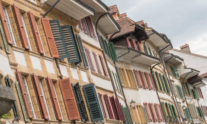Строки на строках старого дома противостоят с милыми окнами и деревянными штарками в много других цветов стоковые изображения