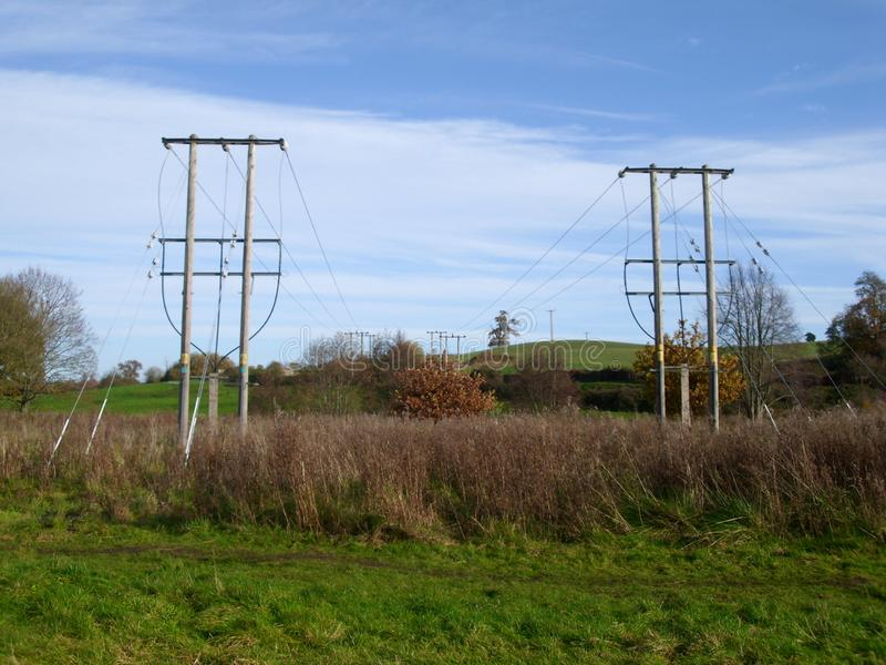 2 строки опор электричества достигая в расстояние стоковые изображения rf
