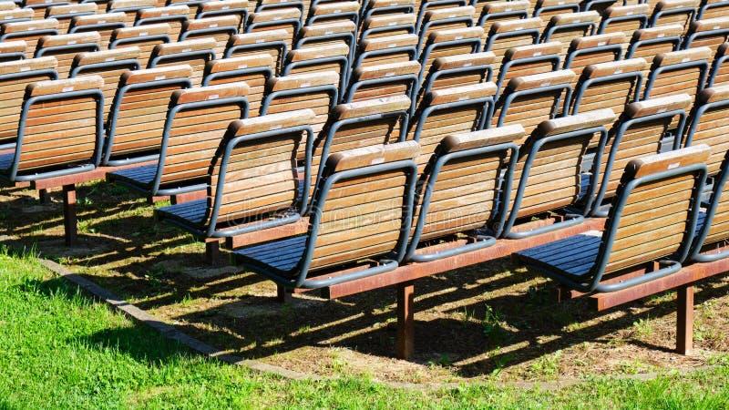 Строки пустых деревянных стульев, выровнянные вверх по снаружи в солнце, на зеленой траве Концепция для событий, сходов, шоу стоковая фотография rf