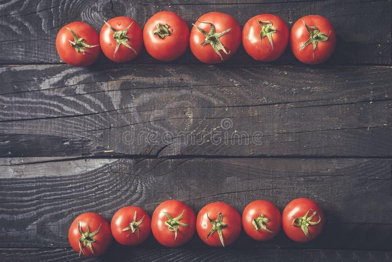 2 строки свежо скомплектованных томатов на темной деревенской деревянной предпосылке стоковые фотографии rf