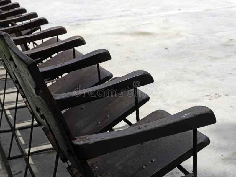 Строки старых деревянных стульев аранжированных в середине солнца мелкое влияние фокуса стоковые изображения
