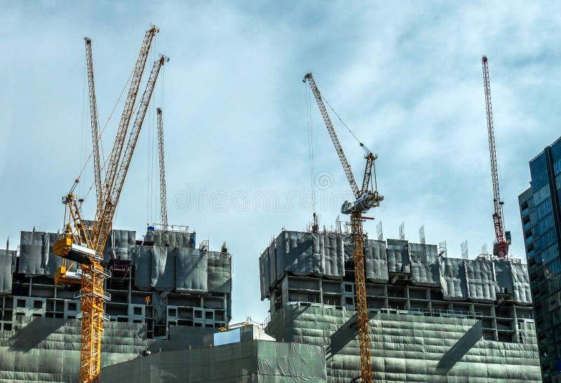 Строя кран и здания под конструкцией и облачным небом, Бангкоком Таиландом стоковые изображения