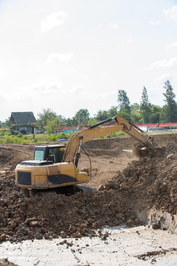 Строя машины: Тележки землекопа нагружая с почвой Песок экскаватора нагружая в самосвал Работа в карьере стоковое фото rf