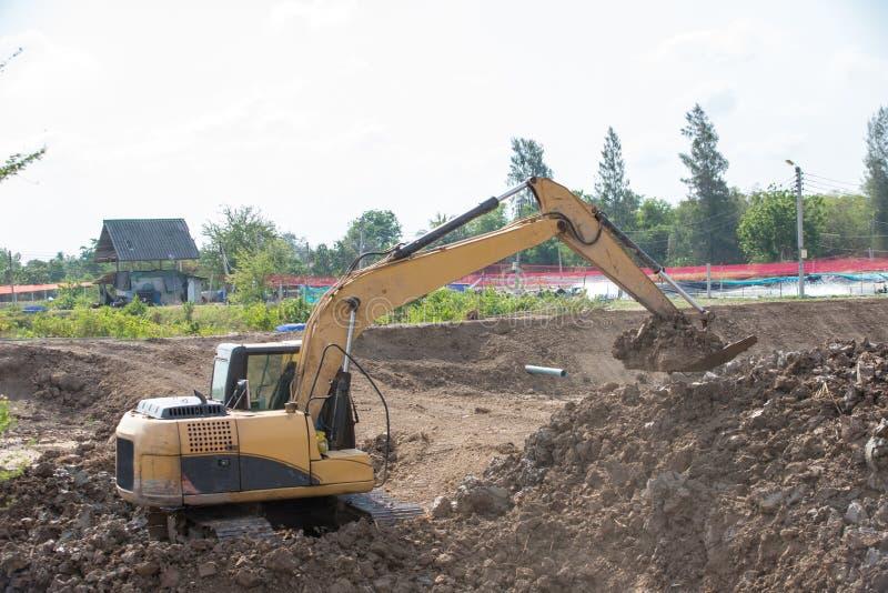 Строя машины: Тележки землекопа нагружая с почвой Песок экскаватора нагружая в самосвал Работа в карьере стоковые изображения rf