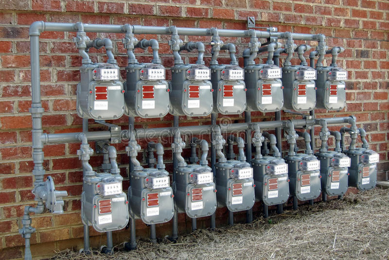 строя стена рядков коммерчески газового счетчика новая стоковые фото