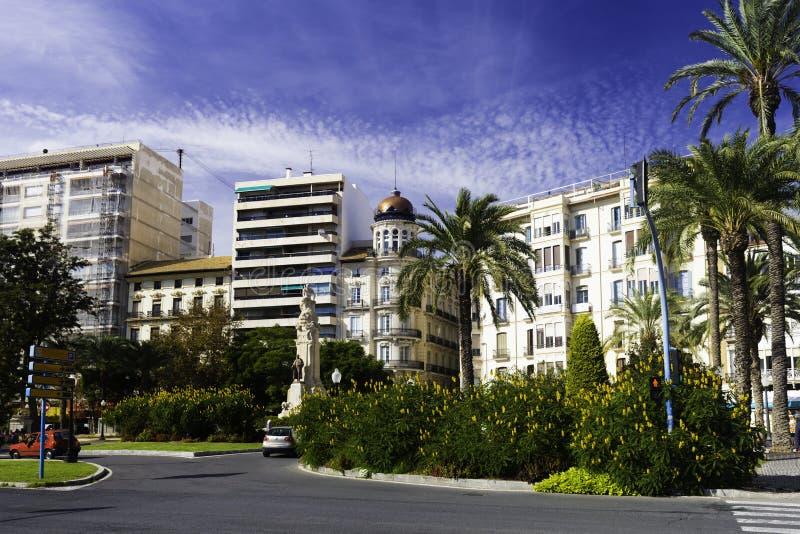 Строя фасады и красивый парк с цветя кустарниками, пальмами на дороге в европейском городе Аликанте внутри стоковое фото rf