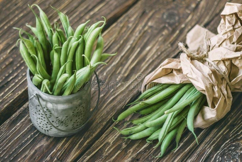 Стручки свежих зеленых фасолей в бумажной сумке и в шаре на деревенском стоковые фото