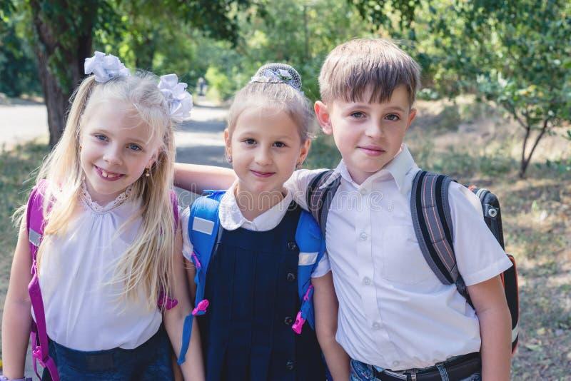 3 студента начальной школы с рюкзаками стоковое изображение