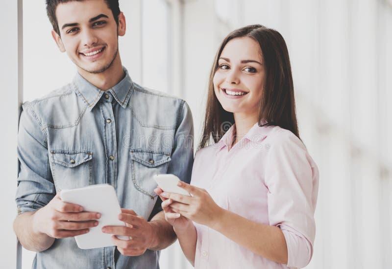 2 студента стоят совместно и держат их устройства стоковое фото