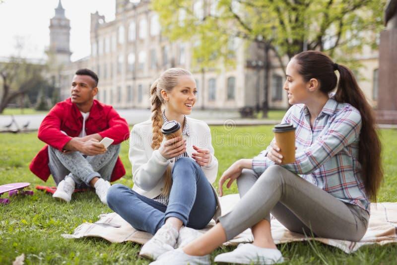 3 студента холостяка наслаждаясь перерывом на чашку кофе совместно стоковое фото rf