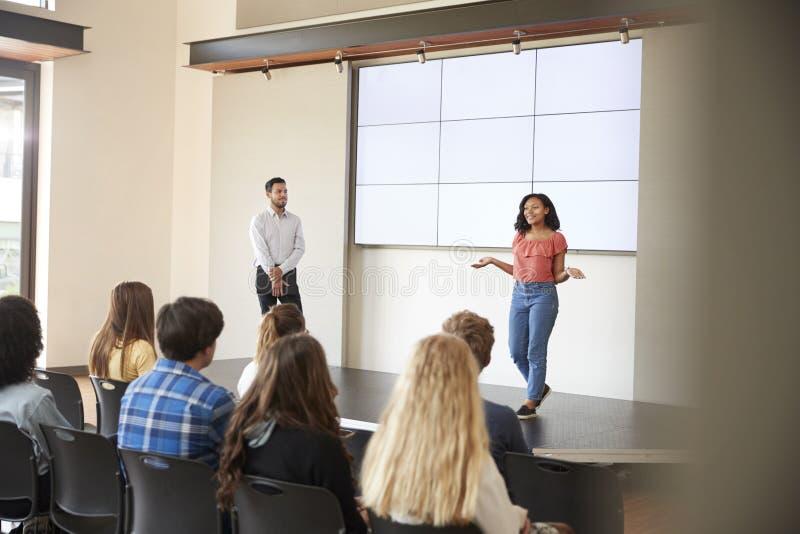 Студентка давая представление к классу средней школы перед экраном стоковое фото rf