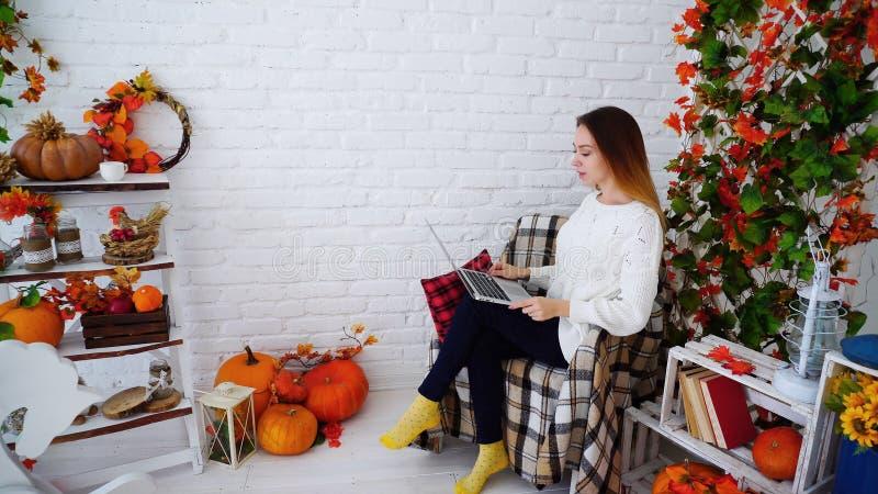 Студентка держа папку и читая домашнюю работу, сидя в стуле против стоковая фотография rf