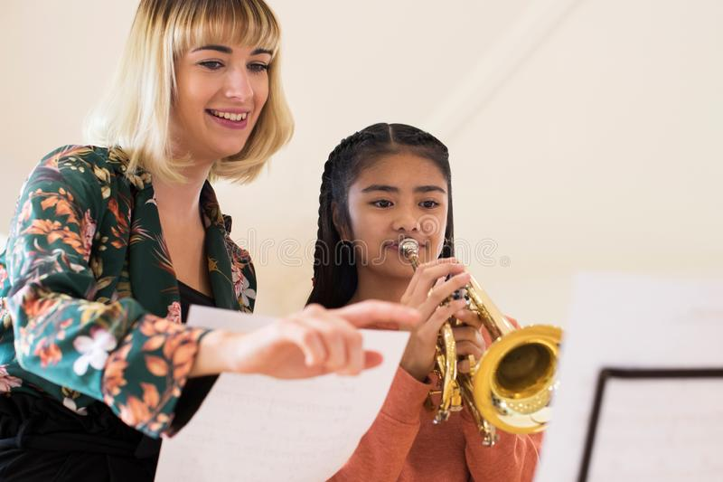 Студентка порции учителя для того чтобы сыграть трубу в уроке музыки стоковые изображения rf