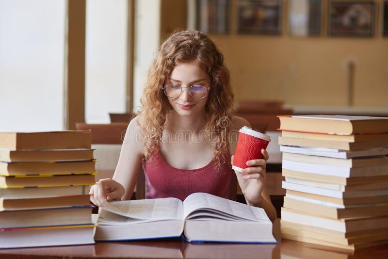 Студентка представляя с кофе в руке, suraunded со стогами книг на reding комнате Молодая женщина сидя на делать таблицы стоковые изображения