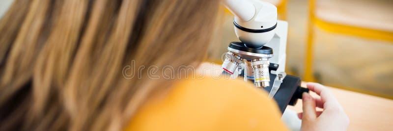 Студентка средней школы в уроке биологии Студент используя микроскоп стоковые изображения