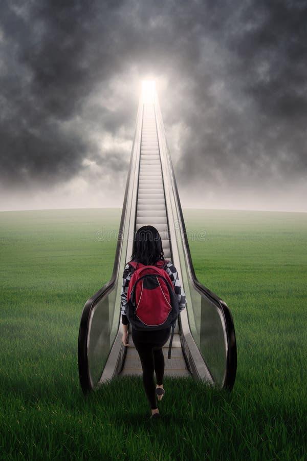 Студентка шагая вверх на эскалатор 1 стоковая фотография