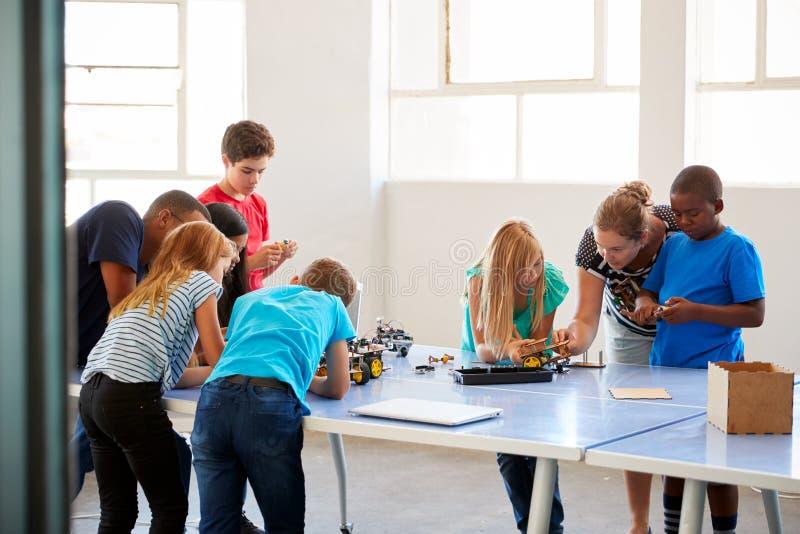 Студенты внутри после здания класса кодирвоания компьютера школы и учить к кораблю робота программы стоковое изображение