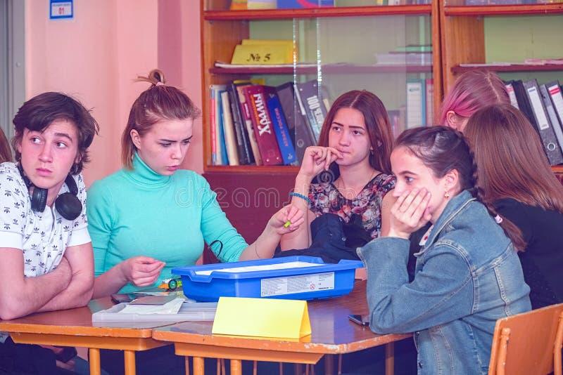 Студенты девушек в классе на их столах стоковые фото