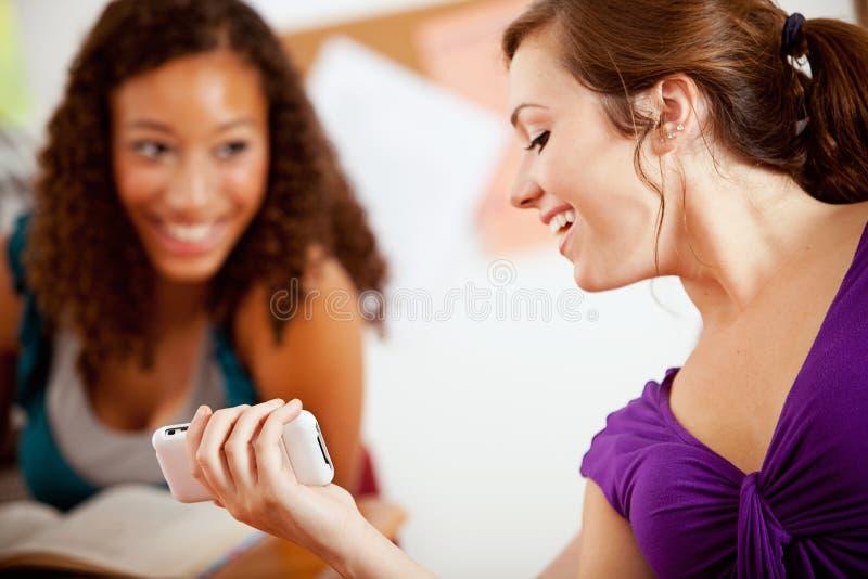 Студенты: Девушка показывает сотовый телефон к другу в классе стоковое фото