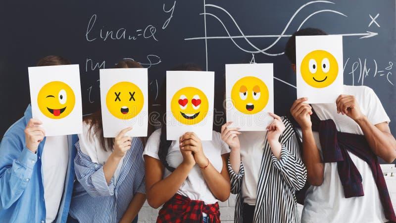 Студенты держа бумаги с эмоциями над доской стоковая фотография