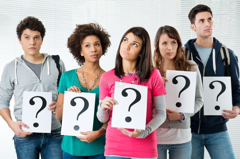 Студенты держа вопросительный знак стоковое фото