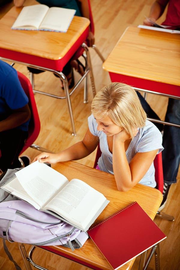Студенты: Жизнерадостная студентка работая на столе стоковые изображения