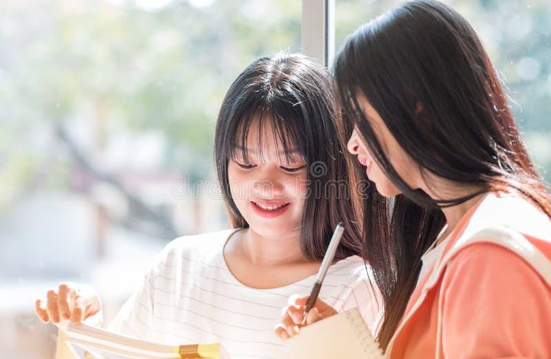 Студенты из Азиатского университета или колледжа учатся вместе с планшетом и документируют статью, чтобы написать отчет возле око стоковое фото