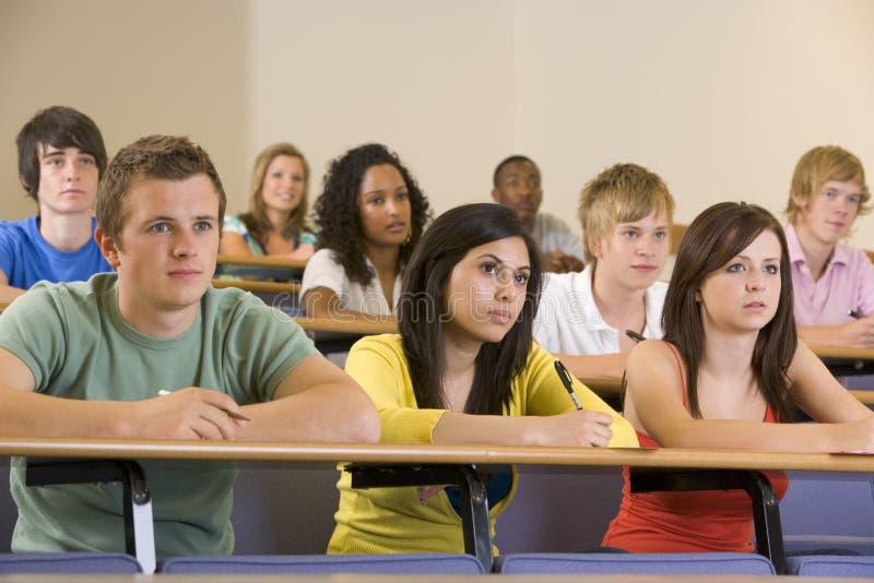 студенты лекции по коллежа слушая к университету стоковая фотография rf