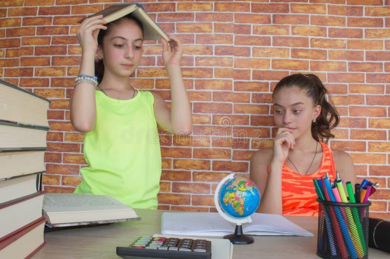 Студенты, маленькая девочка 2 работая на его домашней работе Портрет милого студента средней школы девушки изучая и писать стоковые изображения