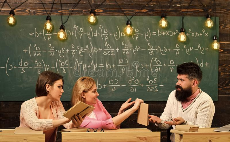 Студенты, молодые ученые изучая, держат книгу, пока профессор учит, объясняют, девушки предпосылки доски стоковые фото