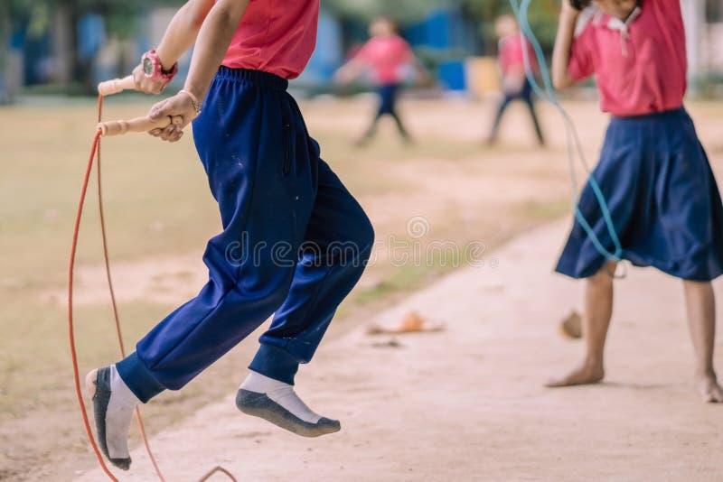 Студенты начальной школы наслаждаются тренировкой скачки веревочки для хорошего hea стоковые фотографии rf