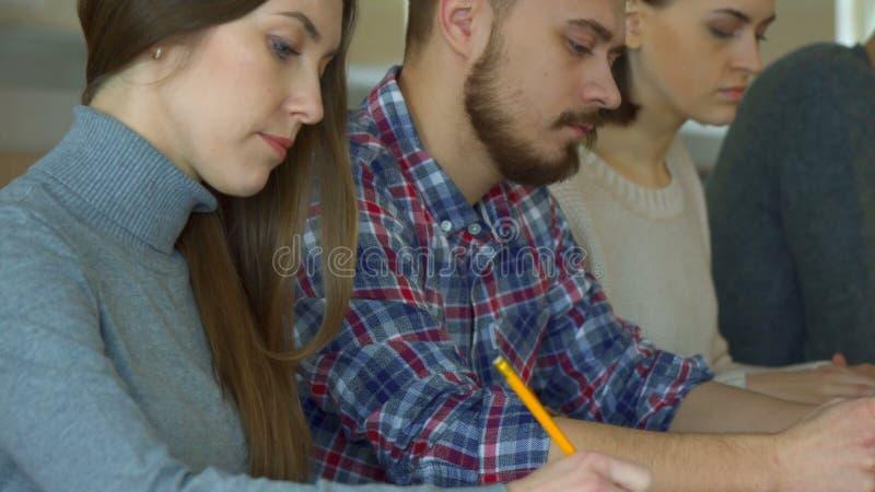 Студенты пишут вниз чего лектор сказал стоковое изображение
