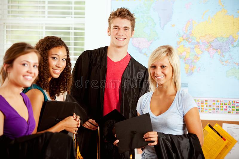 Студенты: Подросток в классе с крышками и мантиями градации стоковая фотография