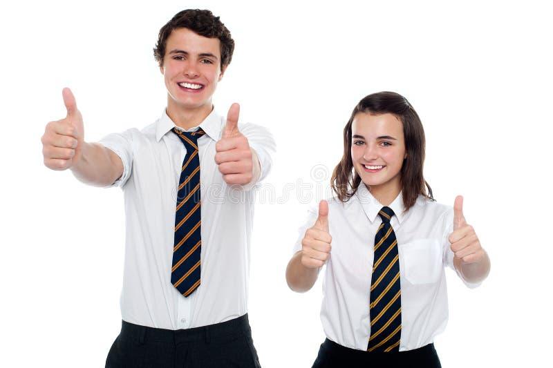 Студенты показывая большие пальцы руки до камеры стоковая фотография rf